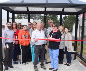 Ruth Moreland, standing next to Depoe Bay mayor, cuts the ribbon on the bus shelter, while her clinic coworkers look on