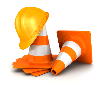 stack of orange traffic cones with a yellow hard hat on top