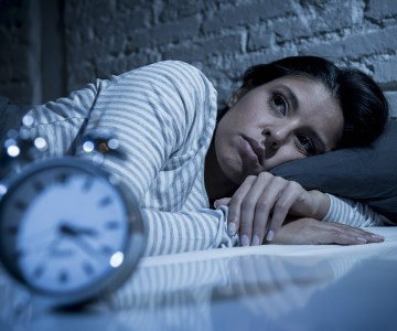 woman in bed wide awake with alarm clock in foreground showing 3:30