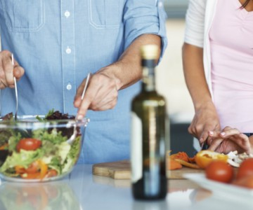 man and woman preparing a salad together