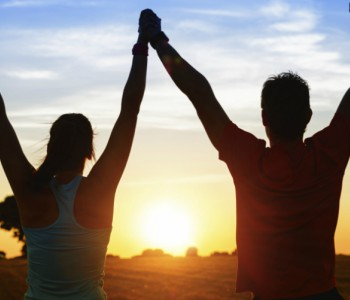 couple silhouetted against the sun with arms upraised in victory