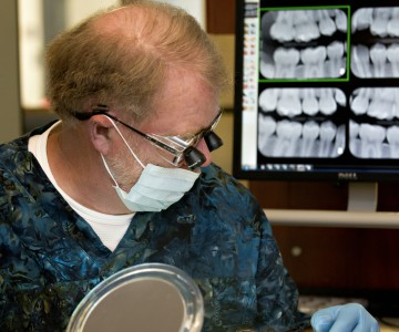 dentist wearing eye magnification looking at patient. Xrays of teeth in background