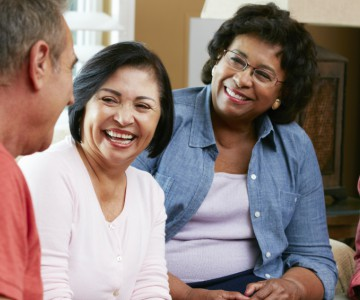 Three older people talking and laughing