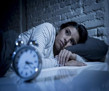 young woman awake at night with clock showing 3:20