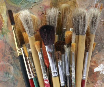 upright group of paintbrushes against colorful background