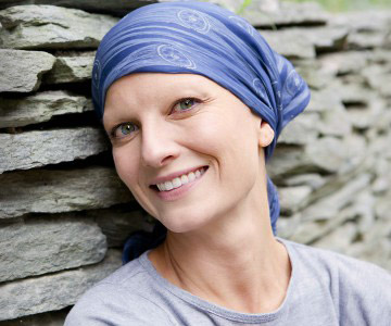 smiling woman with a blue scarf wrapping her head