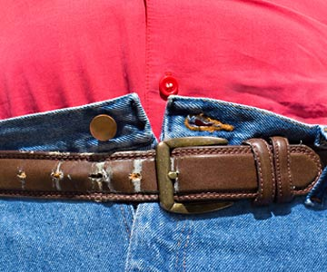 Jeans with top button unbuttoned and belt buckle on the last hole of a belt.