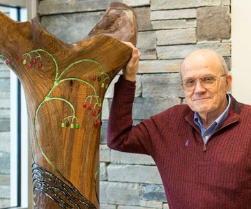 An older gentleman standing with his hand resting on the large wooden sculpture of a tree.