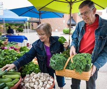 A senior couple buys produce at a farmer