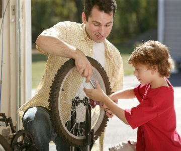 Father and son working together to fix bicycle.