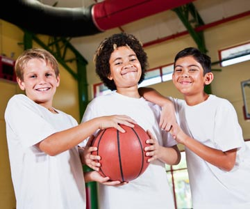 Three kids in a gym holding a basketball.