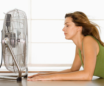 Woman feeling the cool air of a fan.