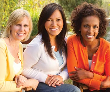 Three smiling women sitting outdoors