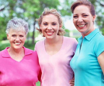 A mother, her teenage daughter and grandmother standing together outdoors.