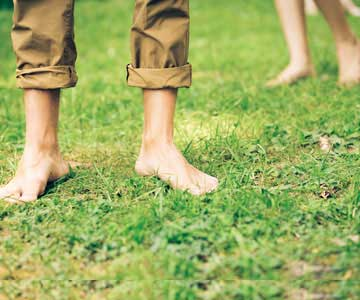 A man and woman walking barefoot in the grass.