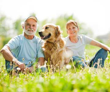 A mature couple relaxing in the grass with their golden retriever.