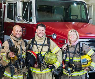 Two male and one female firefighters standing in front of a fire truck.