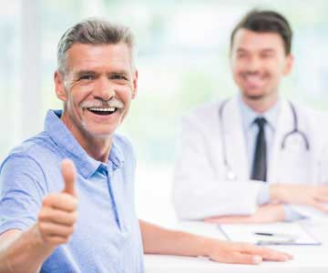 A man giving a thumbs up after his doctor gave him a good check up.