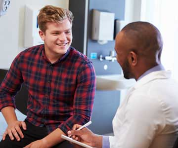 A man smiling and talking with his doctor.