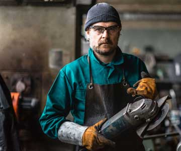 A metalworker in his shop holding a grinder with both hands.