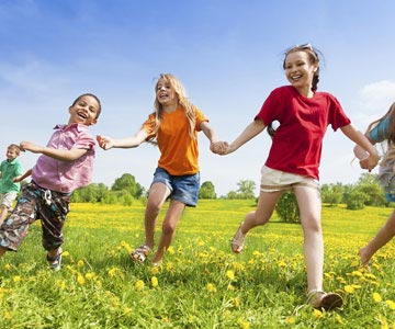 Several young children running through a field full of dandelions.