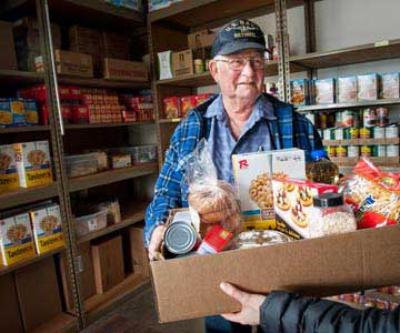 A retired Navy man volunteering at the food bank and handing out food.