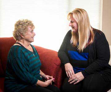Two women visit with each other at the hospice house.