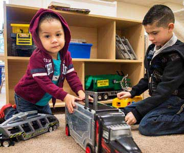 Two young brothers playing with toy trucks at the relief nursery.