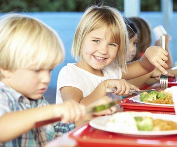 Young kids eating healthy lunches at school.