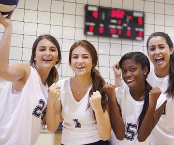 Four young women celebrating after their volleyball game.