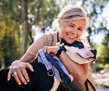 Woman enjoying walk in nature and embracing pet dog in park.