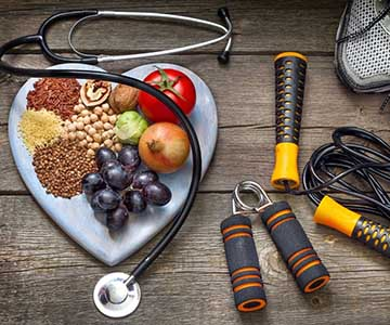 Plate of healthy food with a stethoscope laying over it sitting next to running shoes and a jump rope