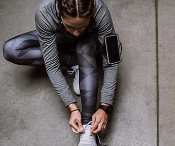 A woman with dark, braided hair in a grey exercise outfit sits on the concrete to tie her running shoes.