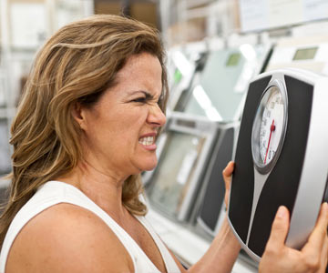 Woman expressing an angry look at her scale.