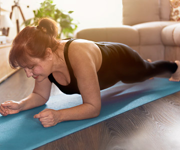 Middle-aged woman performing a plank on a blue yoga mat in her living room.