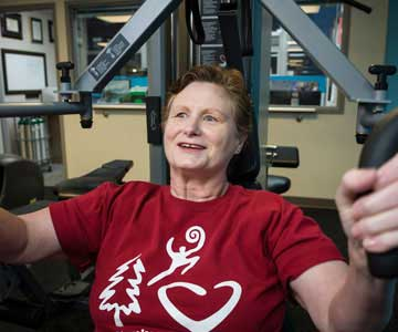 Woman lifting weights wearing red t-shirt with heart on it
