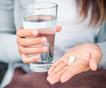 Woman holding a glass of water in one hand and aspirin in the other.