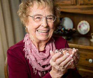 Mary Louise Ray smiles as she holds a glass candleholder that contains a candle that she made.