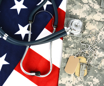 Image of stethoscope laying on top of red, white and blue of a U.S. flag and the desert camouflage, and military dogtags