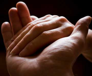 A woman's hand resting in the hand of a man.