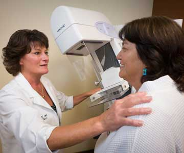 A female doctor talks to a patient with one hand on her shoulder and one on the mammography unit.