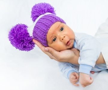 Infant wearing purple knitted hat