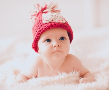 Infant wearing red knitted hat