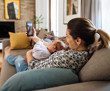 Mom with hair in ponytail lays sits on couch with newborn in her lap while they both look at a cell phone screen.