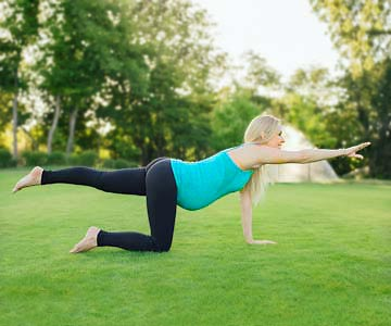 Pregnant woman doing the bird dog to strengthen core muscles.