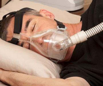 man wearing a CPAP mask over his nose and mouth appears to be sleeping