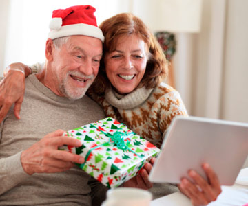 Man and woman talk to family online over the holidays.