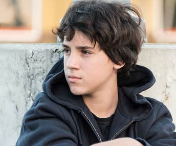 pensive teen boy sitting outdoors
