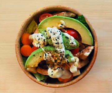 Our Sunny Day Bowl is a delicious combination of fresh veggies quionoa and avocado dressing.