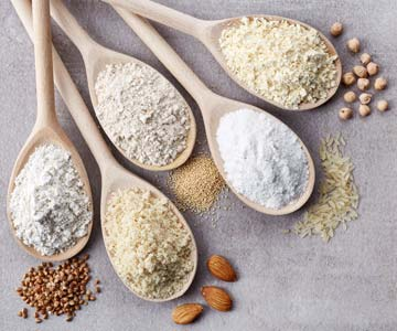 Spoonfuls of gluten free flours: buckwheat, almond, amaranth, rice and chick pea.